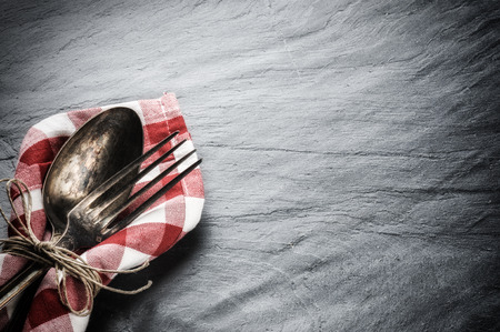 Table setting with vintage spoon and fork on stone background photo