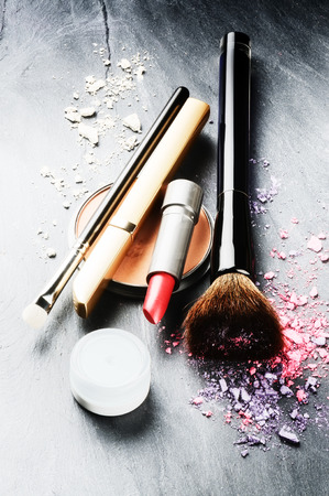 Various makeup products on dark background photo