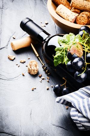 Botella de vino tinto con uva fresca y sacacorchos