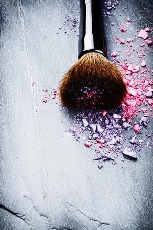 artistas: Cepillo del maquillaje y sombras de ojos aplastados en el fondo oscuro