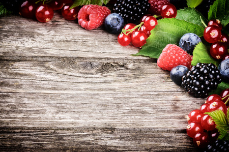 Frame with fresh summer berries on wooden background