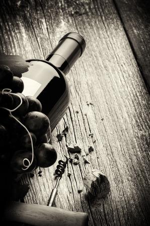 copa de vino: Botella de vino tinto con uva fresca y sacacorchos. Concepto blanco y negro