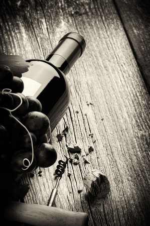Bottle of red wine with fresh grape and corkscrew. Black and white concept