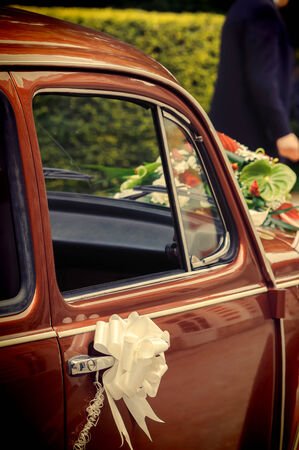 Red vintage car wtih wedding decorations photo