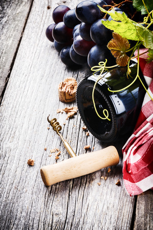 Bottle of red wine with fresh grape on old wooden table photo