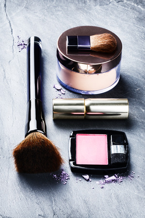compact: Various makeup products on dark background