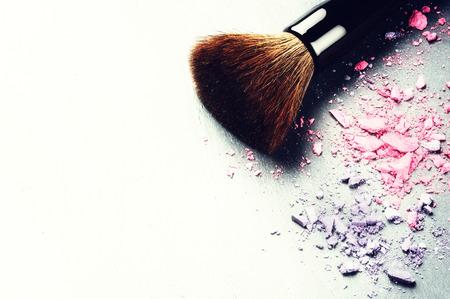 mujer maquillandose: Cepillo del maquillaje y sombras de ojos aplastados sobre fondo claro