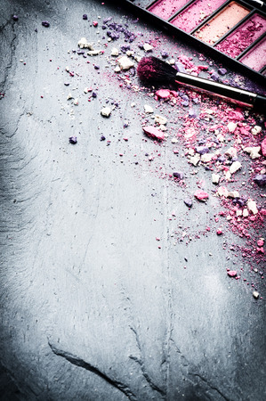 Makeup brush and crushed eyeshadows on stone background 版權商用圖片