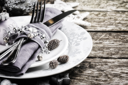 Christmas table setting in silver tone on wooden table photo