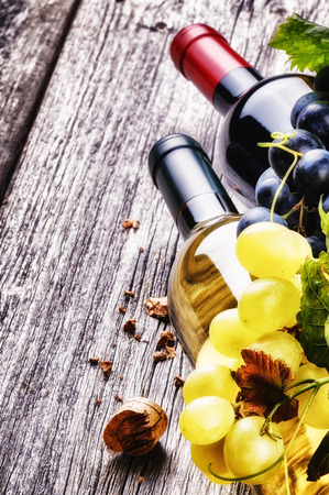 Bottles of red and white wine with fresh grape on old wood background