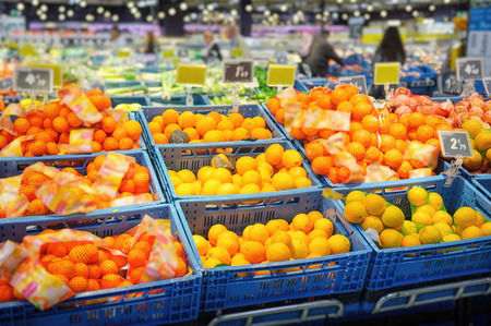 Shelves with various citrus fruits in supermarket photo
