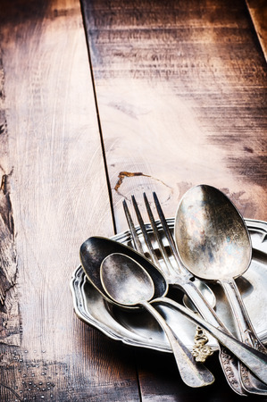 Vintage cutlery on wooden table with copyspace photo