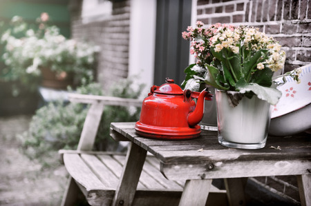 Backyard decoration with vintage kettle and flowers on small wooden table photo