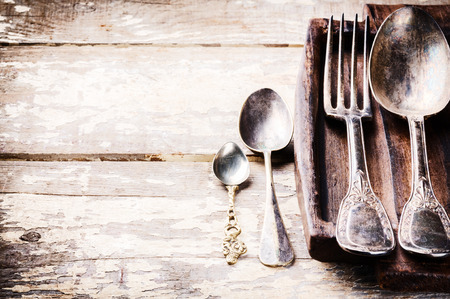 Table setting with vintage cutlery on old wooden table photo