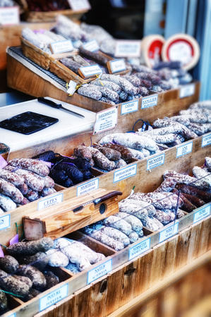 Variety of dried sausages on traditional market counter photo