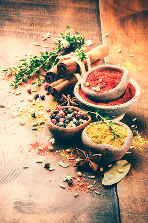 Colorful mix of various spices and herbs on wooden background
