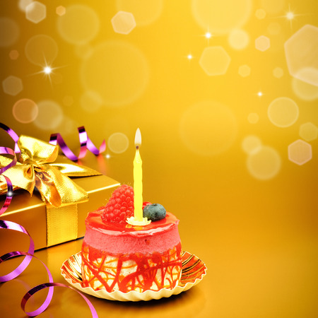 Colorful birthday cake with candle on golden background 版權商用圖片