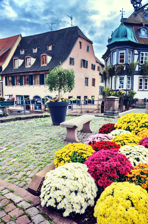 des vins: Small town center decorated with colorful flowers. Alsace, France Stock Photo