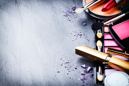 up: Various makeup products on dark background with copyspace Stock Photo