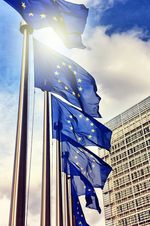 international crisis: European Union flags on blue sky background