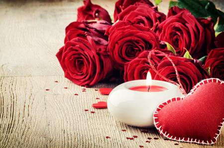 bougie coeur: Le réglage de la Saint-Valentin avec bouquet de roses rouges et bougies