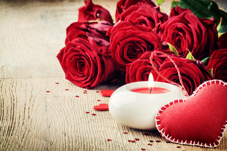 St Valentines setting with bouquet of red roses and candle photo