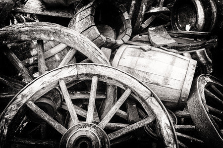 Old wooden barrels and broken wheels in retro setting photo