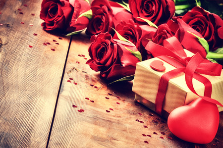 Valentines setting with bouquet of red roses and present in box 版權商用圖片