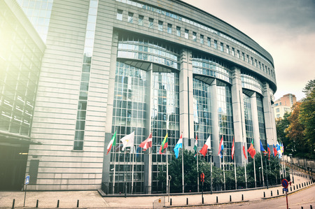 the european economic community: Waiving flags in front of European Parliament building. Brussels, Belgium