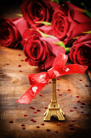 woden: Valentines setting with Eiffel tower decoration and bouquet of red roses on woden background Stock Photo