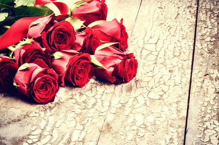 Bouquet of red roses on grunge background. St Valentines concept photo