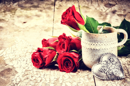 Valentines setting with bouquet of red roses and decorative heart photo