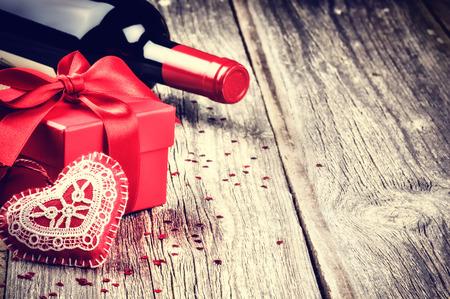 romance: Impostazione di San Valentino con il vino presente e rosso su fondo in legno
