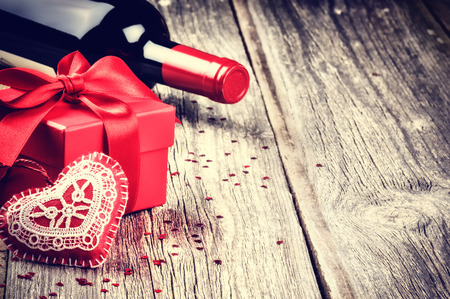 St Valentines setting with present and red wine on wooden background