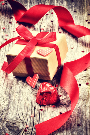 Valentines setting with gift box and red hearts decorations photo