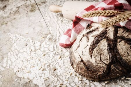 Freshly baked bread loaf in rustic setting with copyspace photo