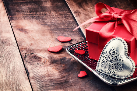Valentines setting with present and heart decoration on wood background