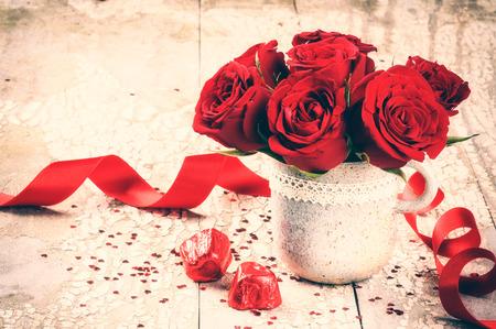 rosas rojas: Entorno de San Valentín con el ramo de rosas rojas y el chocolate en el fondo de madera vieja