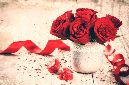 Valentines setting with bouquet of red roses and chocolate on old wood background