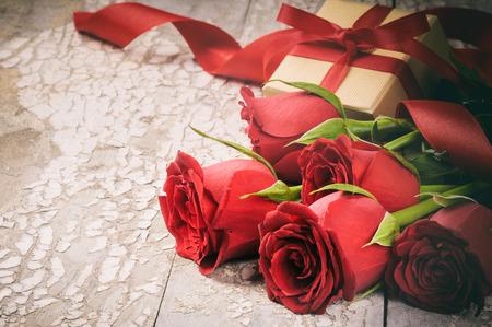 Le réglage de la Saint-Valentin avec bouquet de roses rouges et présent sur fond de bois Banque d'images