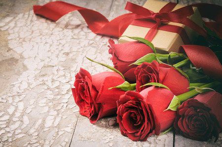 Valentines setting with bouquet of red roses and present on wooden background 版權商用圖片