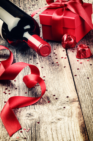 St Valentine's setting with present and red wine on old wood background Foto de archivo