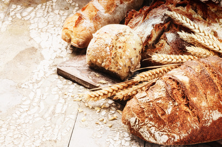 Freshly baked bread in rustic setting on wooden table Stock Photo
