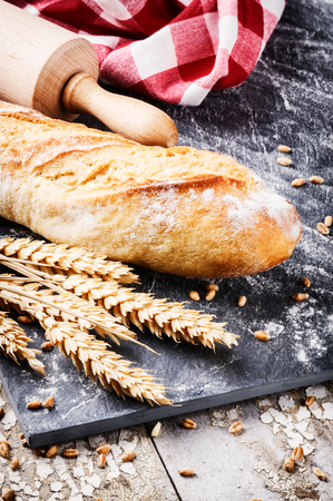 Freshly baked french baguette in rustic setting with wheat photo