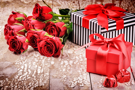Valentine's setting with bouquet of red roses and presents in boxes