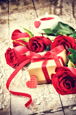 Valentines setting with bouquet of red roses and present in box photo
