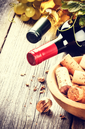 Bottles of red and white wine with bunch of corks and fresh grape photo