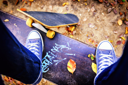 autumn city: Skateboarder standing on a bench in autumn city park Stock Photo