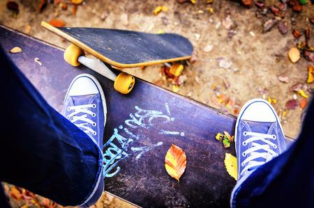 skateboarding: Skateboarder standing on a bench in autumn city park Stock Photo