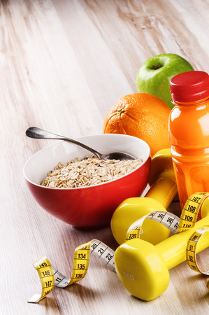 Fitness concept with dumbbells, oatmeal and fresh fruits with juice